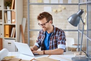 Computer ondernemer shutterstock_281471426ondernemer lachend achter laptop